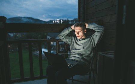 Photo pour Sérieux jeune homme en tenue décontractée s'assoit tard dans la nuit sur le balcon avec un ordinateur portable sur ses genoux, regarde anxieusement l'écran.Guy travaille à l'ordinateur portable sur le balcon à la campagne.Freelance. Échéance - image libre de droit