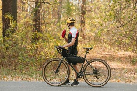 Photo pour Cycliste homme marchant dans le parc d'automne avec une bouteille d'eau à la main et regardant loin. Cycliste professionnel marchant sur la route du parc sur fond de forêt d'automne et d'eau potable. - image libre de droit