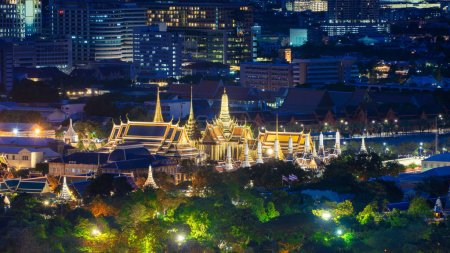 Photo for Temple of the Emerald Buddha, Wat Phra Kaew, and skyscraper buildings. Bangkok downtown area at night, Thailand. Buddhist temple. - Royalty Free Image