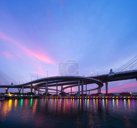 Photo for Reflection of Bhumibol Bridge and Chao Phraya River in structure of suspension architecture concept, Urban city, Bangkok. Downtown area at sunset, Thailand. - Royalty Free Image