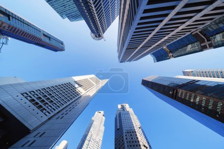Photo for Looking up to high-rise buildings, skyscrapers, architectures in smart city for technology background in Singapore City with blue sky - Royalty Free Image