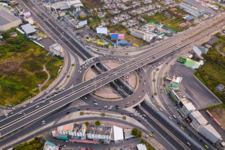 Aerial view of highway junctions with roundabout. Bridge roads shape circle in structure of architecture and transportation concept. Top view. Urban city, Bangkok at sunset, Thailand.