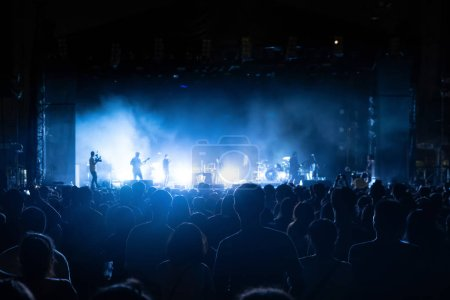 Photo for Silhouettes of crowd, group of people, cheering in live music concert in front of colorful stage lights. - Royalty Free Image