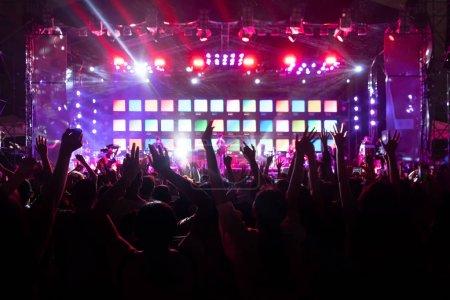 Photo pour Silhouettes de foule, groupe de personnes, acclamations dans un concert de musique en direct devant des lumières de scène colorées . - image libre de droit
