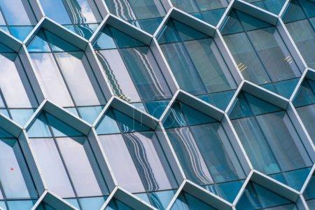 Photo pour Immeubles de bureaux. Structure des fenêtres hexagonales dans le concept de connexion réseau technologique futuriste. Architecture moderne en verre bleu design de façade avec reflet du ciel dans la ville urbaine, Centre-ville . - image libre de droit