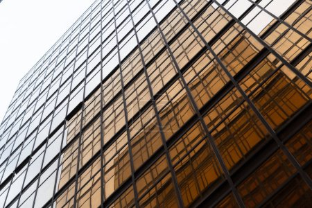 Photo for Golden building. Windows glass of modern office skyscrapers in technology and business concept. Facade design. Construction structure of architecture exterior for urban cityscape background. - Royalty Free Image