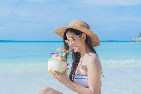 Photo for Happy Asian woman, a sexy Thai lady, drinking coconut water at turquoise sea near Phuket beach during travel holidays vacation trip outdoors at natural ocean or island at noon, Thailand. - Royalty Free Image