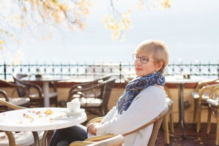 Relaxed senior woman is sitting and resting in autumn street cafe outside. Beautiful retired female person is enjoying life and coffee. Concept of life satisfaction, calm, wellbeing.