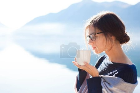 Photo pour Femme buvant du café à la plage. Pique-nique d'hiver confortable. Fille profiter du thé du matin, la vie, Voyage, détente. Fond bleu de montagnes, eau calme. Espace de copie. Portrait féminin - image libre de droit