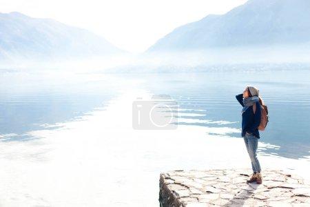 Photo pour Voyageur à la plage de mer d'hiver. Fille avec sac à dos par montagnes bleues et lac. Jeune femme appréciant voyager, vacances, aventure, paysage étonnant. Tourisme féminin en solo. Moment de style de vie. Espace de copie . - image libre de droit