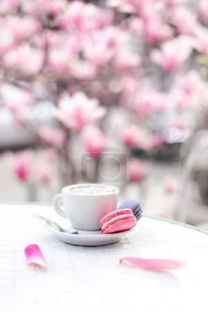 Spring cafe and cup of coffee in pink magnolia flowers. Still life with macaroons and petals