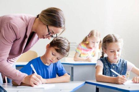 Photo pour Enseignant aidant les élèves à étudier et à écrire. Leçon pour les enfants à l'école primaire. Des enfants assis au bureau en classe. Femme enseignant aux élèves du primaire. Concept de retour à l'école. - image libre de droit