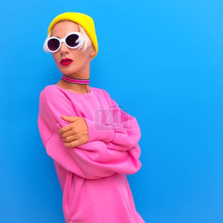 Blonde Girl in fashion accessories. Beanie Cap, Sunglasses and choker. Colorful trendy urban street vibes