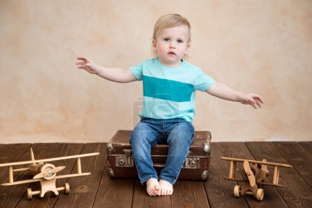 Happy child playing at home. Baby boy with toy airplane. Summer vacation and travel, dream and imagination concept