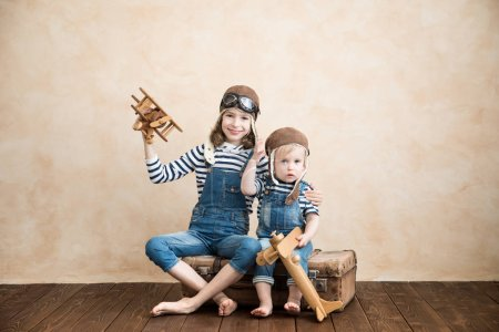 Happy children playing at home. Baby boy and girl with toy airplane. Summer vacation and travel, dream and imagination concept