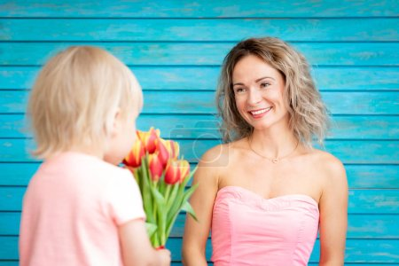 Photo for Son giving tulips to mother at Mothers day - Royalty Free Image