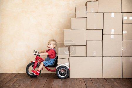 Photo for Happy child playing into new home. Kid driving toy car. Moving day concept - Royalty Free Image