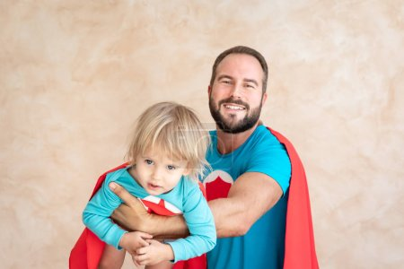Photo for Man and child super hero at home. Superhero father and son having fun together. Family holiday concept. Happy Father's day - Royalty Free Image