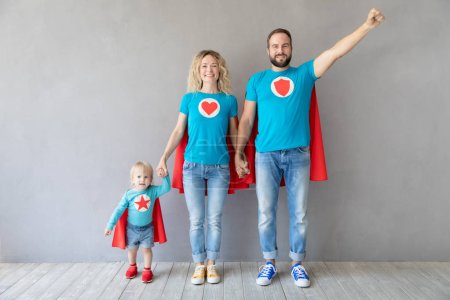 Family of superheroes playing at