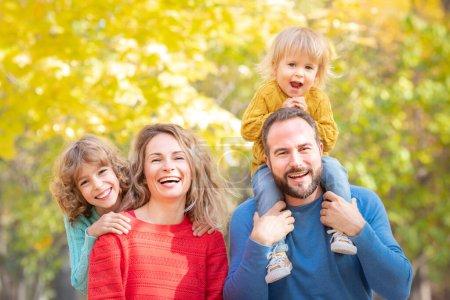 Famille heureuse s'amuser en plein air dans le parc d'automne. Enfants et parents sur fond de feuilles jaunes floues