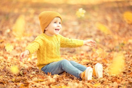 Photo for Happy child having fun outdoor in autumn park. Kid sitting on leaves against yellow blurred background - Royalty Free Image
