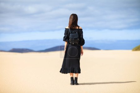 Back view of young lonely woman in long black dress in desert on Canary Islands. Travel concept