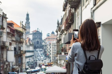 Young traveler woman taking a photo with her phone in Porto, Portugal. Travel concept
