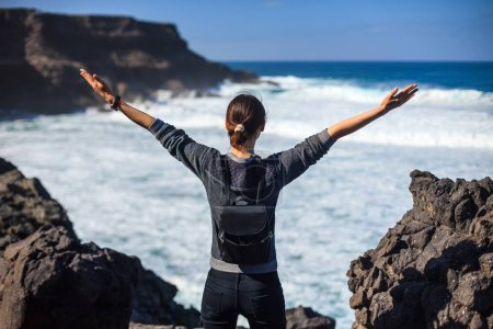 Photo for Freedom traveler woman with raised arms enjoying ocean. success concept - Royalty Free Image