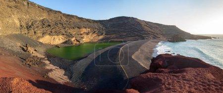 Large panorama of a black beach, volcanic crater with green lake (El Lago Verde, Charco de los Clicos)  in El Golfo. Lanzarote. Canary Islands. Spain