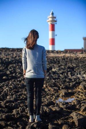 Photo pour Vue arrière de la jeune belle femme appréciant le phare. Concept de mode de vie - image libre de droit