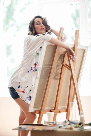 Pretty female artist posing by easel in art studio. Creative concept
