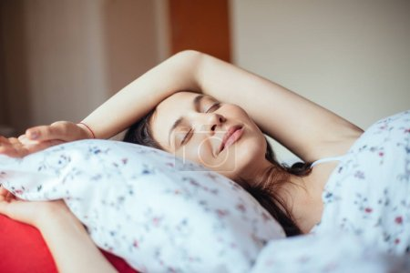 Photo pour Jeune femme souriant tout en dormant dans le lit à la maison. Concept relax - image libre de droit