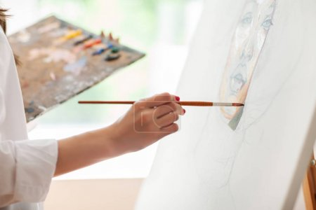 Hand of artist with brush painting picture on canvas in art studio