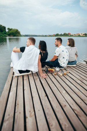 Rear view of group of young friends relaxing on river pier sitting in row.