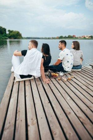 Vista posterior del grupo de jóvenes amigos de relax en el muelle de río sentados en fila