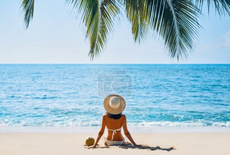 Photo pour Femme bronzer et se détendre assis seul sur la plage tropicale. Concept vacances d'été - image libre de droit