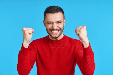 Photo pour Homme heureux célébrant son succès avec un geste gagnant sur fond bleu. concept victoire, triomphe et émotions - image libre de droit