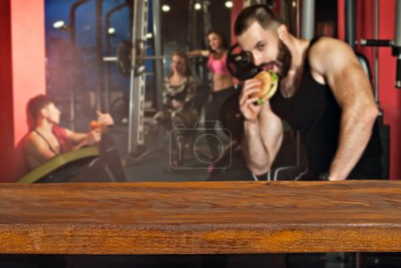 Product display montage Concept. Empty wood table space platform and fitness gym background. Athletes are trained on a blurred background.