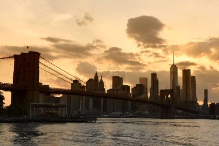 Photo for New York cityscape at sunset. New York City, financial district in lower Manhattan view from Brooklyn Bridge Park. - Royalty Free Image