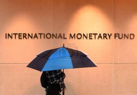 Photo pour Washington, Dc - 4 juin 2018: Piéton avec un parasol près le Fonds monétaire International, FMI siège 2 bâtiment (Hq2) en Dc. - image libre de droit