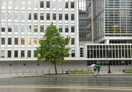 Photo pour Washington, Dc - 4 juin 2018: Piétons avec un parapluie près de bâtiment principal de la Banque mondiale à Washington. - image libre de droit
