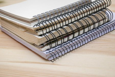 Pile de différents cahiers couchés sur une table en bois
