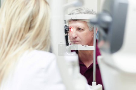 Refractometry. Keratometry. Refraction test. Optometry equipment. Man looking at refractometer eye test machine in ophthalmology, white empty screen