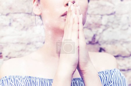 Photo for Young woman in pray with hands clasped in prayer - Royalty Free Image