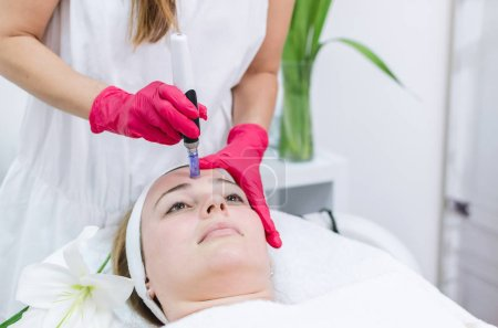 Hardware cosmetology, mesotherapy. Processing of the forehead area on beautiful young woman.