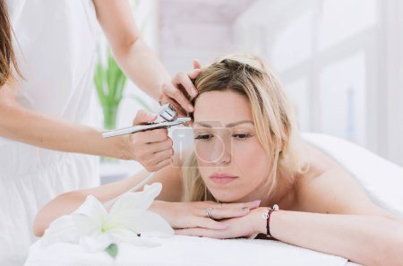 Front View Of Beautiful Woman Receiving Face Oxygen Peeling At Cosmetology Center. Girl Enjoying Skin Rejuvenation Procedure. Beauty Treatment Concept.