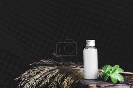 Front view of small full glass vial with liquid on black background, medicine concept, one object