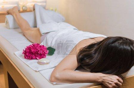 Photo pour Belle jeune femme couchée sur tabel spa et en attente de jambe et pied massage au spa salon de beauté. - image libre de droit