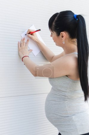 Vertical image of beautiful young pregnant woman, standing and writing something down on piece of blank paper.