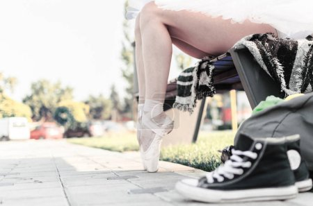Photo for Cropped image of young ballerina sitting on bench, outdoors. - Royalty Free Image